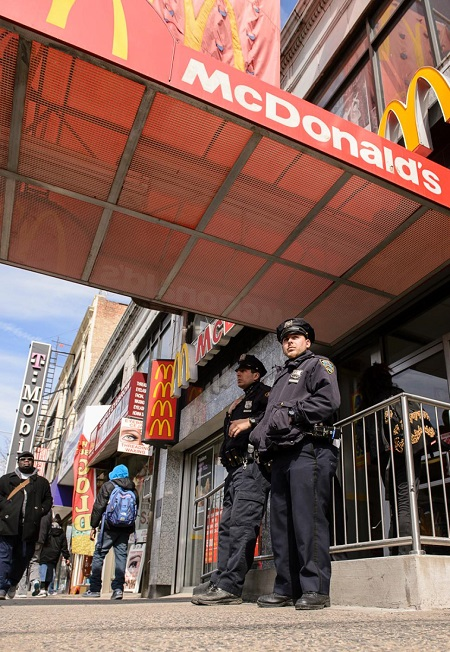 Police officers stand outside the McDonald's on Flatbush Ave. where the attack took place.